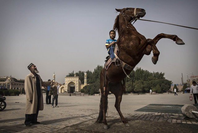 A Uyghur boy sits atop a horse as he has his picture taken outside the Id Kah Mosque before the Eid holiday  on July 28, 2014 in old Kashgar, Xinjiang Province, China. (Photo by Kevin Frayer/Getty Images)