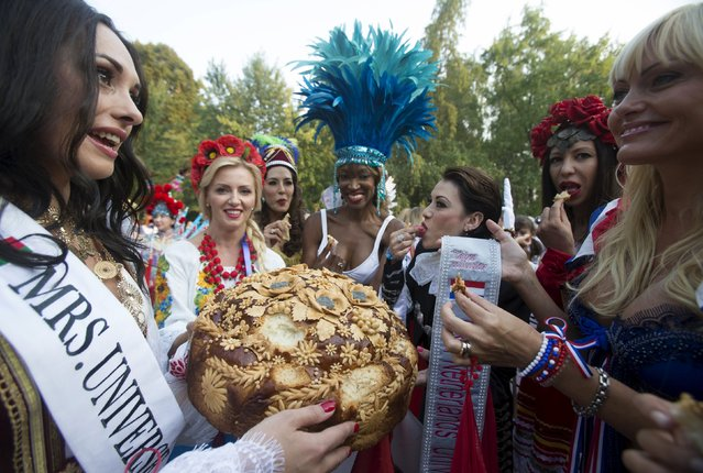 """Participants of the """"Mrs Universe 2015"""" contest are seen with a loaf during their visit in central botanical garden in Minsk, Belarus, August 25, 2015. (Photo by Vasily Fedosenko/Reuters)"""