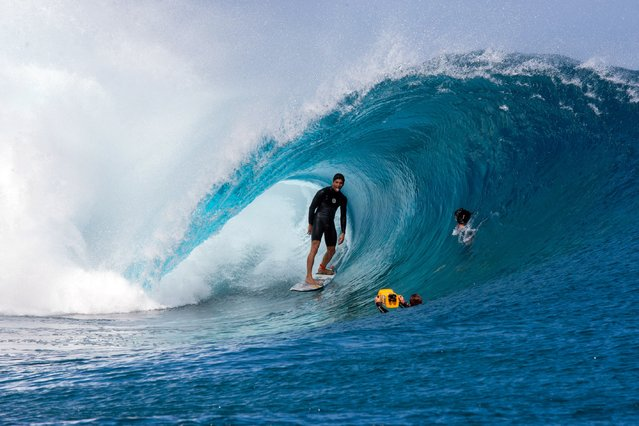 Cameramen float in the water filming Brazil's Gabriel Medina sticking out his tongue before competing in the World Surf league tour n°4, as part of the 2015 Billabong Pro Tahiti, along the Teahupo'o coast, western of the French polynesia island of Tahiti, on August 24, 2015. (Photo by Gregory Boissy/AFP Photo)