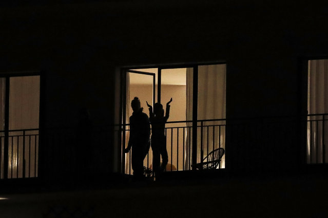 People applaud the caregivers for their work, as the coronavirus ravaged communities across the country, in Ville d'Avray, outside Paris, Thursday, March 19, 2020. In France at 8pm sharp local time French citizens leaned out of windows and dangled from balconies and began applauding and whistling in unison to thank those on the front lines of the pandemic that has already claimed scores of lives. (Photo by Christophe Ena/AP Photo)