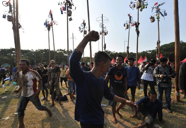 "A team celebrates after claiming all the prizes in a local competition called ""panjat pinang"" in which they had to be the first to climb a greased pole and reach the top, during an event to celebrate Indonesia's Independence Day in Jakarta on August 17, 2014. (Photo by Adek Berry/AFP Photo)"