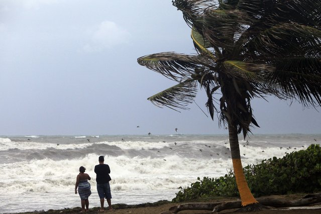 A couple looks out at a rough sea as Tropical Storm Erika moves away from the area in Guayama, Puerto Rico, Friday, August 28, 2015. The storm was expected to dump up to 8 inches of rain across the drought-stricken northern Caribbean as it carved a path toward the U.S. (Photo by Ricardo Arduengo/AP Photo)