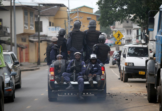 Members of Liberia's Ebola Task Force ride in the back of a pickup as they enforce a quarantine on the West Point slum on August 20, 2014 in Monrovia, Liberia. (Photo by John Moore/Getty Images)