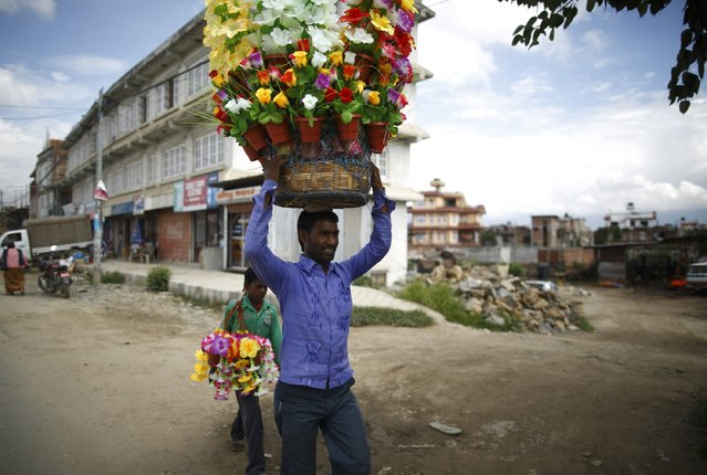 A street vendor carrying plastic flowers walks along the street to sell them in Lalitpur August 18, 2014. (Photo by Navesh Chitrakar/Reuters)