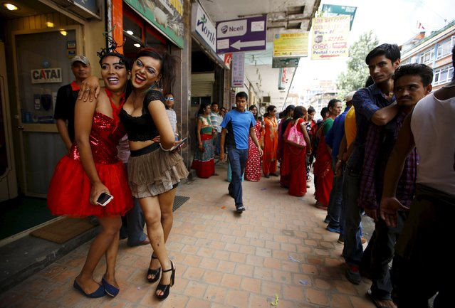 People look at revellers (L) waiting to take part in a LGBT (lesbian, gay, bisexual and transgender) pride parade to mark Gaijatra Festival, also known as the festival of cows, in Kathmandu, Nepal, August 30, 2015. (Photo by Navesh Chitrakar/Reuters)