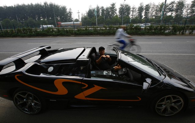 Wang Yu gestures in a handmade replica of Lamborghini Diablo as a cyclist passes by on a street during a test drive in Beijing, August 21, 2014. (Photo by Petar Kujundzic/Reuters)