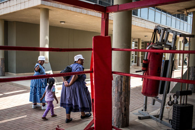 "Some of the ""Boxing Gogos"" (Grannies) walk home with one of their grandchildren after a training session hosted by the A Team Gym in Cosmo City in Johannesburg on September 19, 2017. (Photo by Gulshan Khan/AFP Photo)"