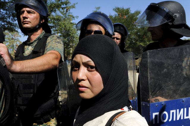 A migrant stands in front of Macedonian special police forces as she waits to cross Greece's border with Macedonia, near the village of Idomeni, September 2, 2015. Migrants are trekking from the southern Macedonian border with Greece, near Gevgelija, to the northern border with Serbia on their way to Western Europe. (Photo by Alexandros Avramidis/Reuters)