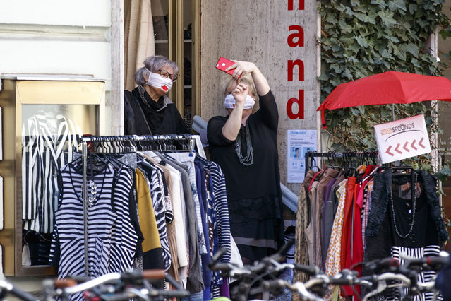Women wearing masks take selfies outside a shop as businesses reopen following a shutdown in a measure to limit the spread of the virus in Graz, Austria on April 14, 2020. (Photo by Erwin Scheriau/APA/AFP Photo)