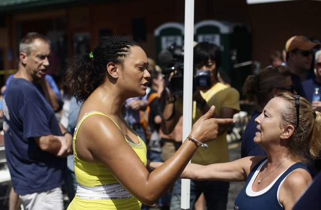 Sondra Fifer (C) confronts demonstrators supporting Ferguson Police officer Darren Wilson during a rally in St. Louis, Missouri August 23, 2014. Demonstrators in Ferguson, Missouri, gathered in intense heat on Saturday to pray and mark two weeks since a white police officer shot dead an unarmed black teenager, while supporters of the officer said in a separate rally miles away that the shooting was justified. (Photo by Joshua Lott/Reuters)