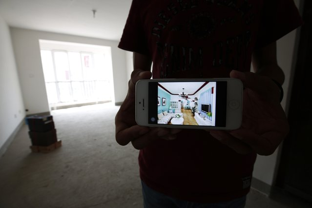 Zhiliang, whose fiancee who was onboard Malaysia Airlines Flight MH370 which disappeared on March 8, 2014, shows an image on his mobile phone, which his fiancee chose for the reference to decorate their newly purchased house, during an interview with Reuters in Tianjin, August 26, 2014. Zhiliang said he will wait for his missing fiancee forever. They had planned to marry this year. (Photo by Kim Kyung-Hoon/Reuters)