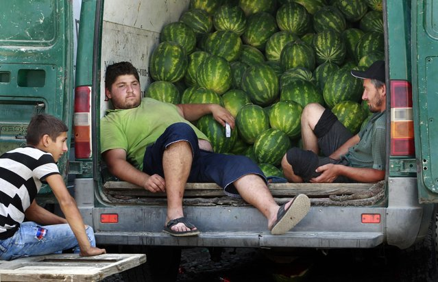 Georgian men take a break from selling fruit and vegetable at a street market in Tbilisi, Georgia, Wednesday, July 20, 2016. (Photo by Shakh Aivazov/AP Photo)