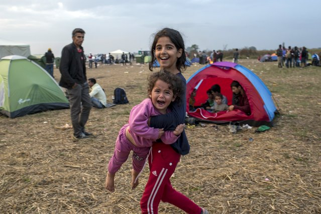A migrant girl carries a child after crossing into Hungary from the border with Serbia on a field near the village of Roszke, September 5, 2015. (Photo by Marko Djurica/Reuters)