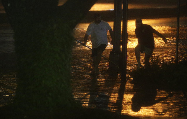 David Amerson, left, and T.J. Krueger, right, wade through a flooded street during Hurricane Nate, Sunday, October 8, 2017, in Mobile, Ala. Hurricane Nate came ashore along Mississippi's coast outside Biloxi early Sunday, the first hurricane to make landfall in the state since Hurricane Katrina in 2005. (Photo by Brynn Anderson/AP Photo)