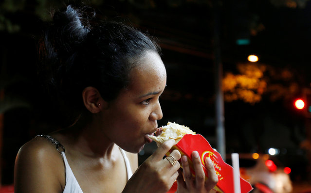"""A woman eats a podrao, the Portuguese word for """"rotten"""" (a hotdog or burger type sandwich assembled according to taste), in Rio de Janeiro, Brazil, April 8, 2016.. (Photo by Sergio Moraes/Reuters)"""