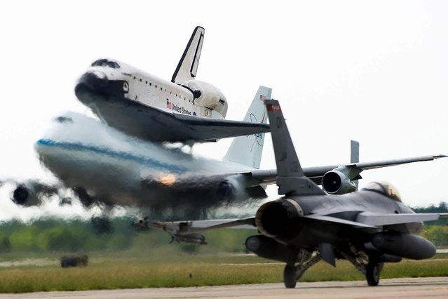 The space shuttle Endeavour, carried atop NASA's 747 Shuttle Carrier Aircraft, lands at Houston's Ellington Field past an aircraft from the Texas Air National Guard 147th Reconnaissance Wing on September 19, 2012. (Photo by Smiley N. Pool/Houston Chronicle)