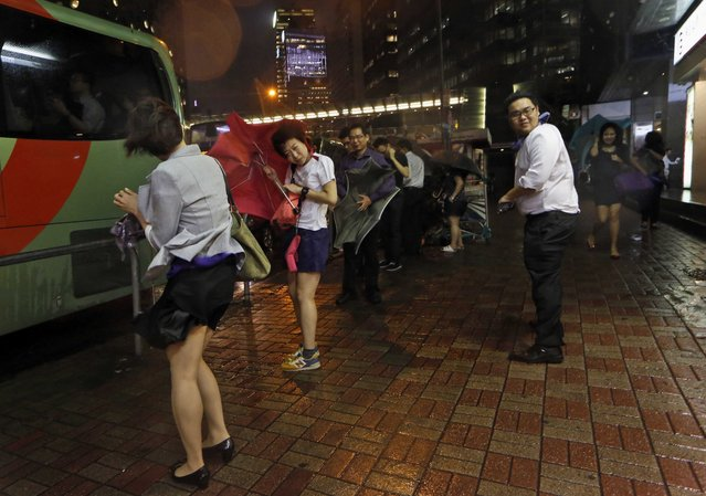 Passengers brave the strong winds as they wait for a bus, in Hong Kong, Monday, September 15, 2014. The Hong Kong Observatory issued the number 8 southeast storm signal, as Typhoon Kalmaegi edges closer to Hong Kong. (Photo by Kin Cheung/AP Photo)
