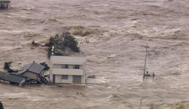 In this photo taken from video provided by Japan's Tokyo Broadcasting System (TBS) television network, a man, right, stands stranded in the middle of raging floodwaters before being rescued by a military helicopter in Joso, Ibaraki prefecture, Thursday, September 10, 2015. (Photo by TBS TV via AP Photo)