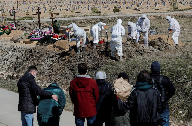 Mourners gather near grave diggers wearing personal protective equipment (PPE), who bury a coronavirus disease (COVID-19) victim in the special purpose section of a graveyard on the outskirts of Saint Petersburg, Russia on May 5, 2020. (Photo by Anton Vaganov/Reuters)