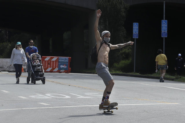 A man wears a face mask while skateboarding on a closed street at Golden Gate Park during the coronavirus outbreak in San Francisco, Sunday, May 17, 2020. (Photo by Jeff Chiu/AP Photo)