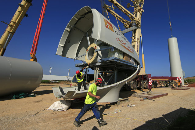 Employees work on the nacelle of a turbine in Meneslies, France July 17, 2014. (Photo by Benoit Tessier/Reuters)