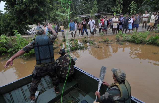 Indian Army personnel conducting rescue operation in the flood affected Chaygaon village in Kamrup district of Assam state, India, 23 September 2014. At least 22 people have been killed in floods and landslides in north-eastern India, officials said and an estimated 200,000 people were affected as the floods that damaged roads, bridges and homes in states of Meghalaya and Assam. (Photo by EPA/Stringer)
