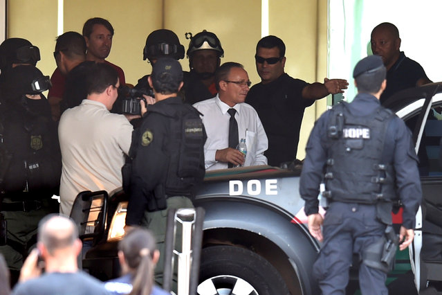 A hotel employee (C white shirt) who earlier today was held hostage and forced to wear an explosive-laden vest is driven out from the hotel in Brasilia on September 29, 2014. (Photo by Evaristo Sa/AFP Photo)