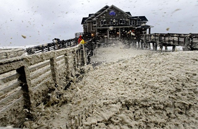 High winds blow sea foam onto Jeanette's Pier in Nags Head, North Carolina as wind and rain from Hurricane Sandy move into the area on Sunday. (Photo by Gerry Broome/Associated Press)