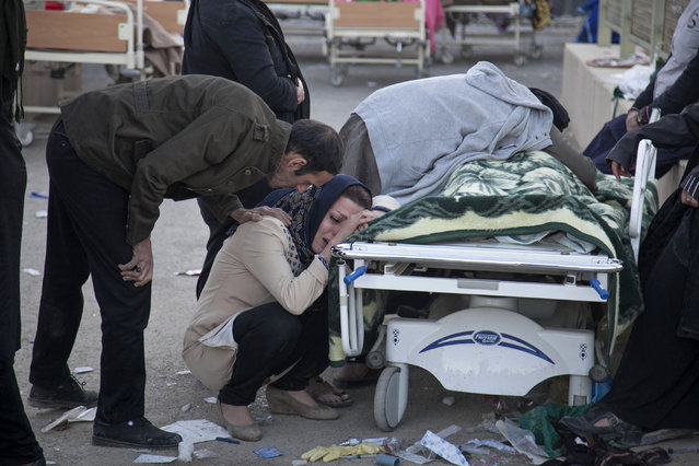 In this photo provided by Tasnim News Agency, relatives weep over the body of an earthquake victim,  in Sarpol-e-Zahab, western Iran, Monday, November 13, 2017. (Photo by Farzad Menati/Tasnim News Agency via AP Photo)