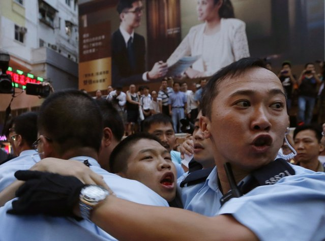 A pro-democracy protester (C) bleeds in the month as he is escorted by the police after being beaten by anti-Occupy Central protesters at Hong Kong's shopping Mongkok district, where a main road is occupied, October 3, 2014. Cracks are beginning to show in public support for Hong Kong's pro-democracy movement, as residents count the cost of a week of sometimes violent disruption to their lives at work and home. (Photo by Bobby Yip/Reuters)