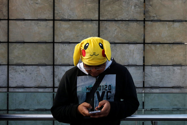 "A man wearing a Pikachu hat, a character from Pokemon, plays Pokemon Go during a gathering to celebrate ""Pokemon Day"" in Mexico City, Mexico August 21, 2016. (Photo by Carlos Jasso/Reuters)"