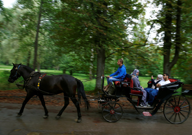 Tourists from the Middle East are driven in horse carriages at Vrelo Bosne nature park in Ilidza near Sarajevo, Bosnia and Herzegovina, August 19, 2016. (Photo by Dado Ruvic/Reuters)
