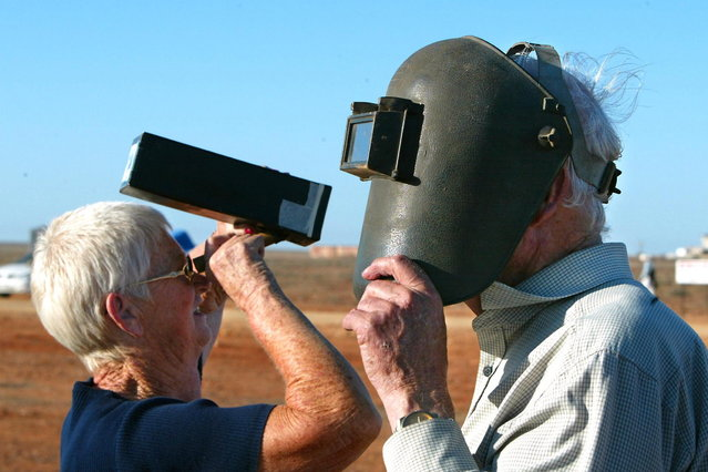 Rod (R) and Greta Handmar (L) use different techniques to observe Australia's first total solar eclipse in 26 years at Koolymilka north of the outback town of Woomera, 04 December 2002, in central Australia. Koolymilka is in a tiny 32 kilometre-wide umbral band running across the desolate state of South Australia which witnessed the eclipse shortly before sunset at 1940 local time. (Photo by Torsten Blackwood/AFP Photo)