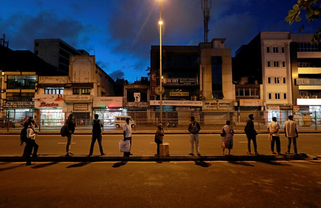 People wearing masks practice social distancing as they line up for public transport to go home at the end of a working day, after an island-wide daytime curfew has been lifted to restart the country's economic activities following almost two-month lockdown amid concerns about the spread of the coronavirus disease (COVID-19), in Colombo, Sri Lanka, June 3, 2020. (Photo by Dinuka Liyanawatte/Reuters)