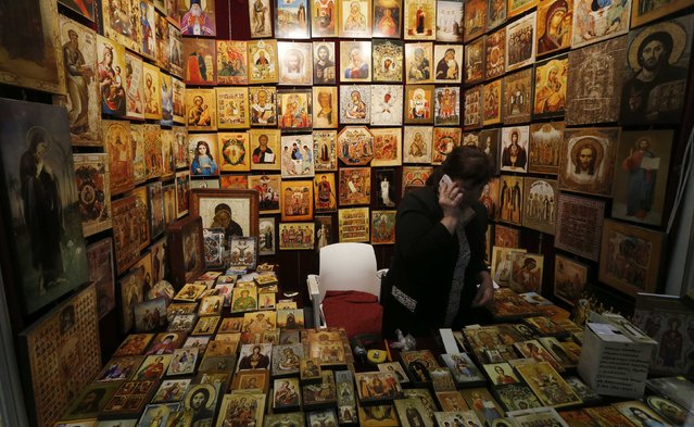 """A participant speaks on the phone as she sells icons during the """"Orthodox Russia"""" (Pravoslavnaya Rus) exhibition in St. Petersburg October 9, 2014. The exhibition attracted participants from several Orthodox countries, including Russia, Ukraine, Belarus, Greece, Montenegro, Georgia, Moldova, who gathered to discuss religious issues and to demonstrate items of spiritual and cultural value, according to organizers. (Photo by Alexander Demianchuk/Reuters)"""