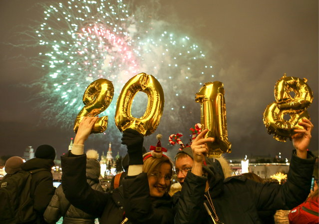People hold up balloons shaped as digits 2, 0, 1 and 8 as they watch fireworks over central Moscow during New Year celebrations on December 31, 2017. (Photo by Marina Lystseva/TASS via Getty Images)