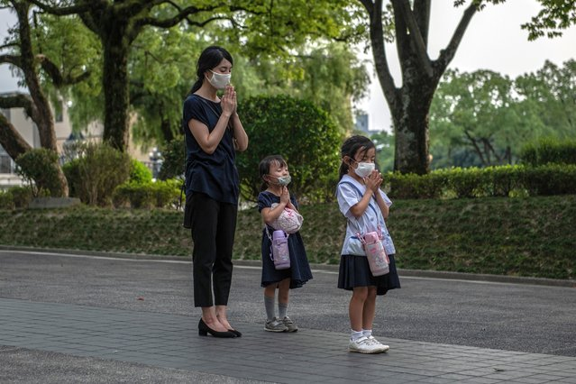 A mother and her daughters pray at the Students Peace Monument on the 75th anniversary of the Hiroshima atomic bombing, on August 6, 2020 in Hiroshima, Japan. In a ceremony that has been scaled back significantly because of Covid-19 coronavirus, Japan will mark the 75th anniversary of the first atomic bomb that was dropped by the United States on Hiroshima on August 6, 1945. The bomb instantly killed an estimated 70,000 people and thousands more in coming years from radiation effects. Three days later the United States dropped a second atomic bomb on Nagasaki which ended World War II. (Photo by Carl Court/Getty Images)