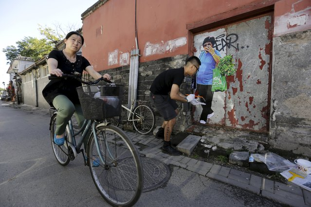 Chinese artist ROBBBB pastes his work on a closed door in a traditional alleyway, or hutong, in central Beijing September 25, 2015. (Photo by Jason Lee/Reuters)