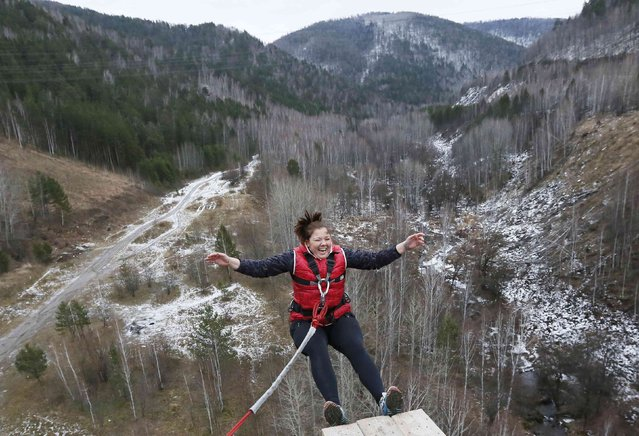 """A member of the amateur rope-jumping group """"Exit Point"""" jumps from a 44-metre high (144-ft) waterpipe bridge in the Siberian Taiga area outside Krasnoyarsk, November 2, 2014. (Photo by Ilya Naymushin/Reuters)"""