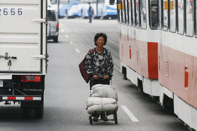 A woman pushes a cart between vehicles in downtown Pyongyang, North Korea October 8, 2015. Smartphones, traffic jams and modern, energy-saving lights casting a dim glow on the streets - North Korea's capital shows signs of change even as it prepares for a pageant of military muscle and propaganda of the kind the country is know for. (Photo by Damir Sagolj/Reuters)
