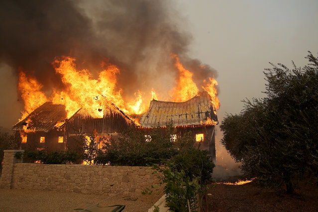 Fire consumes a barn as an out of control wildfire moves through the area on October 9, 2017 in Glen Ellen, California. Tens of thousands of acres and dozens of homes and businesses have burned in widespread wildfires that are burning in Napa and Sonoma counties.  (Photo by Justin Sullivan/Getty Images)