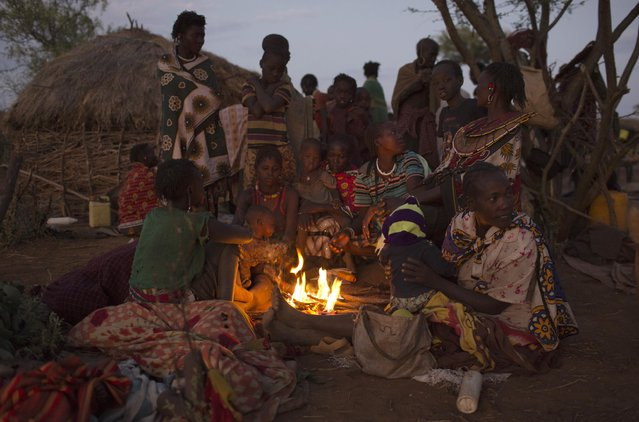 Pokot women and children rest by a fire during the early hours of the morning as they wait for the beginning of a circumcision ceremony, about 80 kilometres from the town of Marigat in Baringo County, Kenya, October 16, 2014. (Photo by Siegfried Modola/Reuters)