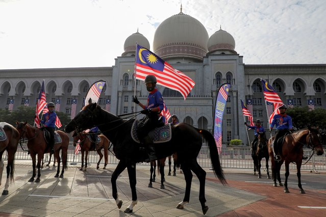 Horse riders holding Malaysian flag take part in a rehearsal for the Independence Day event, in Putrajaya, Malaysia on August 28, 2020. (Photo by Lim Huey Teng/Reuters)