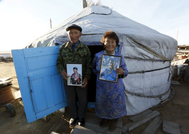 Herder and farmer Stai-ool Ondar (L), 77, and his wife Sendin Ondar, 77, pose for a picture with portraits near a yurt at their family farm located near the Cheder Lake outside the village of Kur-Cher in Tuva region, Southern Siberia, Russia, October 8, 2015. The region is inhabited by Tuvans, historically cattle-herding nomads, who nowadays practise two main confessions - Buddhism and Shamanism. (Photo by Ilya Naymushin/Reuters)