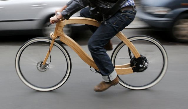 Matthias Broda, inventor and designer of the wooden e-bike, cycles a prototype along a street in Berlin, November 20, 2014. The wooden e-bike produced by German company Aceteam from ash wood, will be launched on the market by spring 2015 and will cost around 3,950 euro (4,950 dollars). The e-bike will be equipped with an 250W e-bike motor for a range of up to 100 kilometer  (62 miles) with a rechargeable battery. (Photo by Fabrizio Bensch/Reuters)