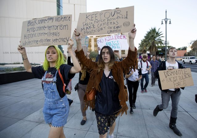 Activists hold signs during a protest march  in Los Angeles, California, following Monday's grand jury decision in the shooting of Michael Brown in Ferguson, Missouri, November 25, 2014
