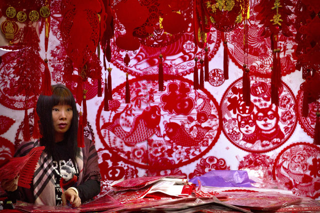 In this Tuesday, February 13, 2018, file photo, a vendor selling Lunar New Year decorations waits for customers at a wholesale market in Beijing. (Photo by Mark Schiefelbein/AP Photo)