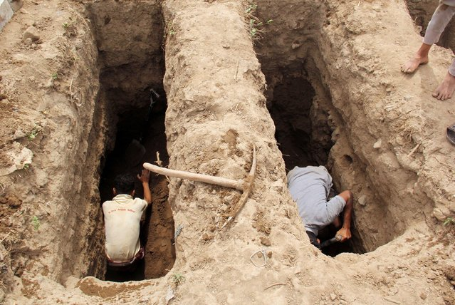 People dig graves at a cemetery where victims of the coronavirus disease (COVID-19) are buried in Taiz, Yemen on June 23, 2020. (Photo by Anees Mahyoub/Reuters)