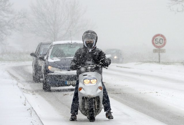 A man rides a scooter on the road N117 around Paris, on March 12, 2013, during a heavy snow storm on France. A heavy late-winter snowstorm hit northwestern Europe on Tuesday, paralysing transport, knocking out power to thousands and leaving hundreds stranded in their cars. (Photo by Franck Fife/AFP Photo)