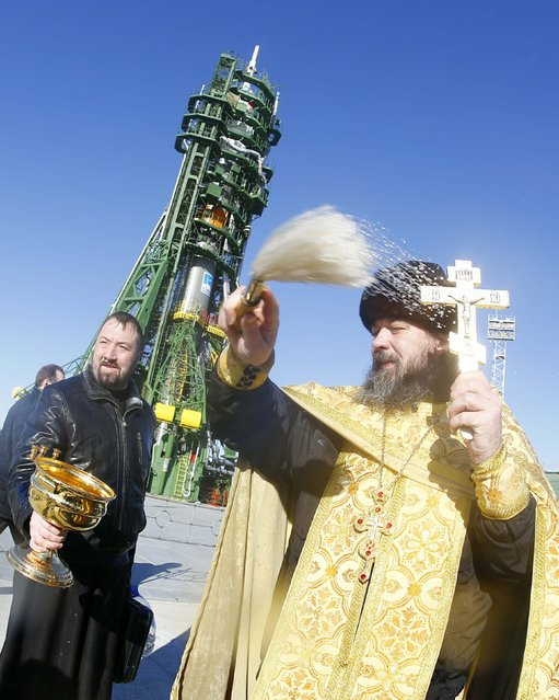 An Orthodox priest conducts a blessing in front of the Soyuz TMA-15M spacecraft set on the launch pad at Baikonur cosmodrome November 22, 2014. The Soyuz is scheduled to blast off with Anton Shkaplerov of Russia, Terry Virts of the U.S. and Samantha Cristoforetti of Italy to the International Space Station on November 24, 2014. (Photo by Shamil Zhumatov/Reuters)